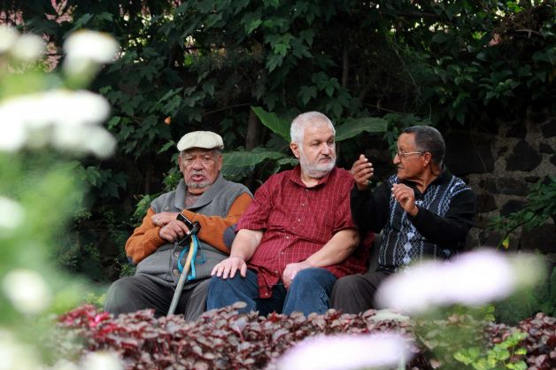 Armenians Paul Donigian, left, and Yohannes Vorperiam, center, sit with an unidentified person at right, in a garden in Addis Ababa, Ethiopia. Photo: Elias Asmare, AP